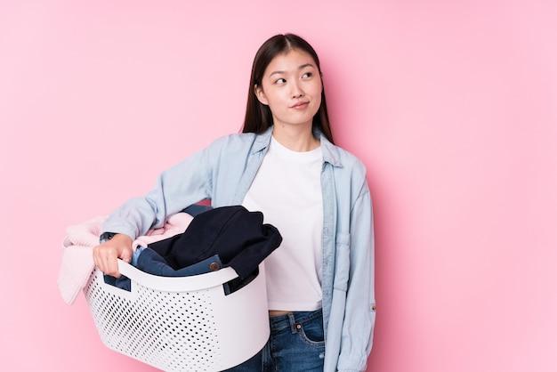 Joven china recogiendo ropa sucia soñando con lograr objetivos y propósitos