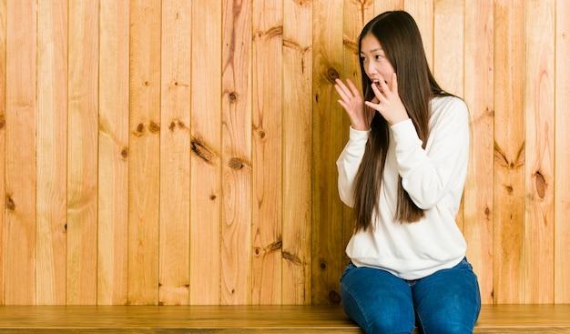 Joven china sentada en un lugar de madera grita fuerte, mantiene los ojos abiertos y las manos tensas.