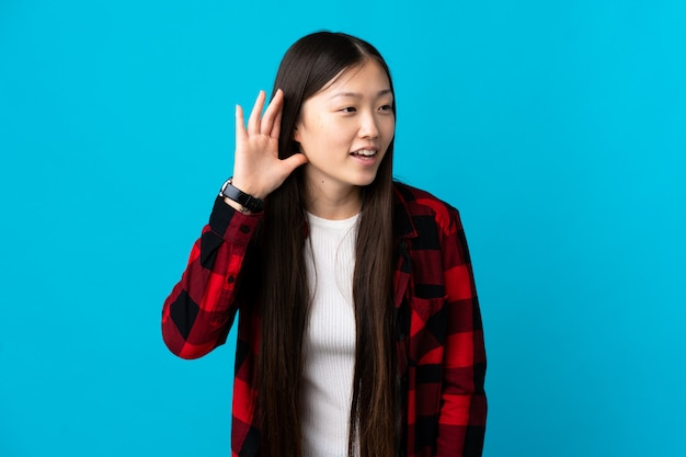 Joven china sobre pared azul aislada escuchando algo poniendo la mano en la oreja