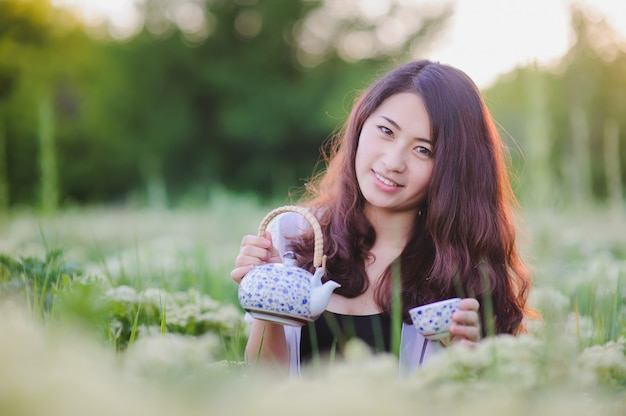 Joven china vierte té en prado floreciente