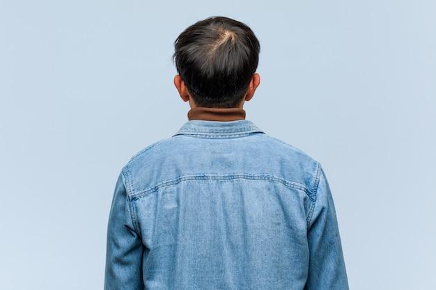 Joven chino desde atrás, mirando hacia atrás