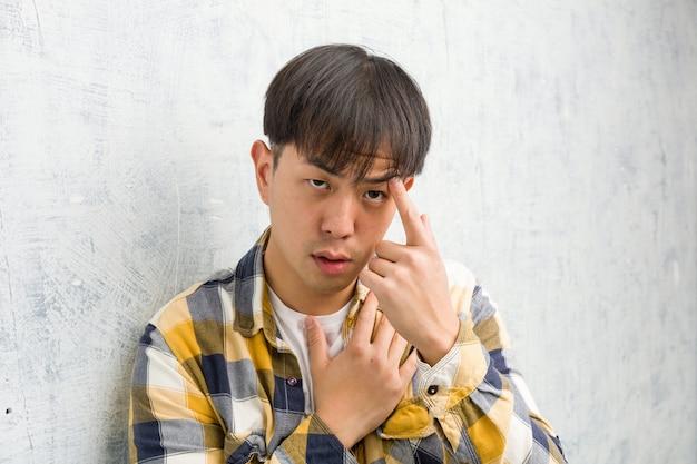 Joven chino cara closeup haciendo un gesto de decepción con el dedo