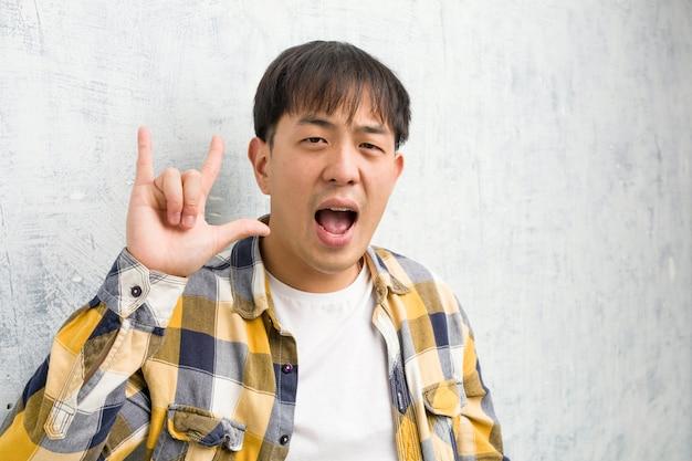 Joven chino cara closeup haciendo un gesto de rock