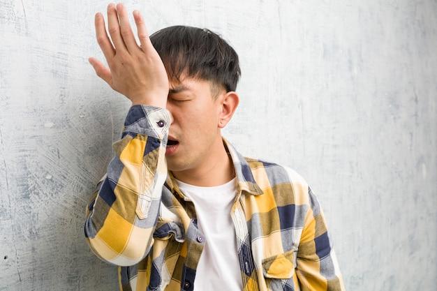 Joven chino cara closeup olvidadizo, darse cuenta de algo