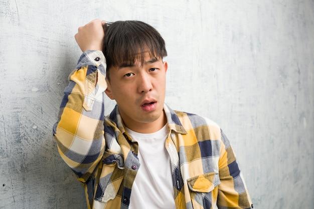 Joven chino cara closeup preocupado y abrumado