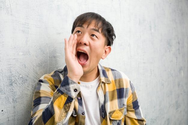 Joven chino cara closeup susurrando matices de chismes