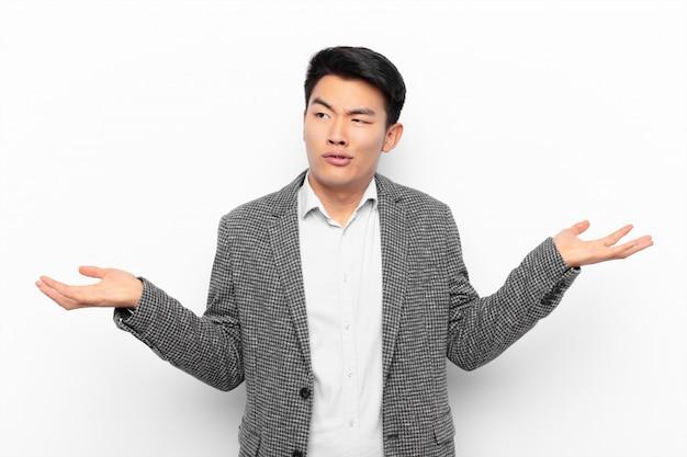 Joven chino encogiéndose de hombros con una expresión tonta, loca, confundida y perpleja, sintiéndose molesto y desorientado contra la pared de color plano