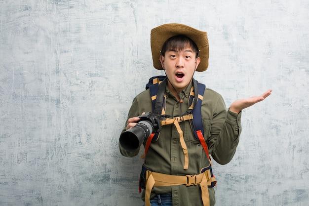 Joven chino explorador hombre sosteniendo una cámara sosteniendo algo en la mano de la palma