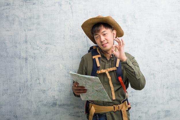 Joven chino explorador hombre sosteniendo un mapa alegre y seguro haciendo gesto bien