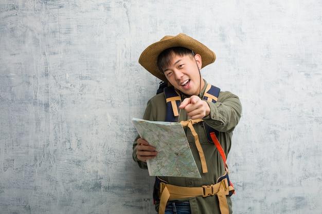 Joven chino explorador hombre sosteniendo un mapa alegre y sonriente apuntando al frente