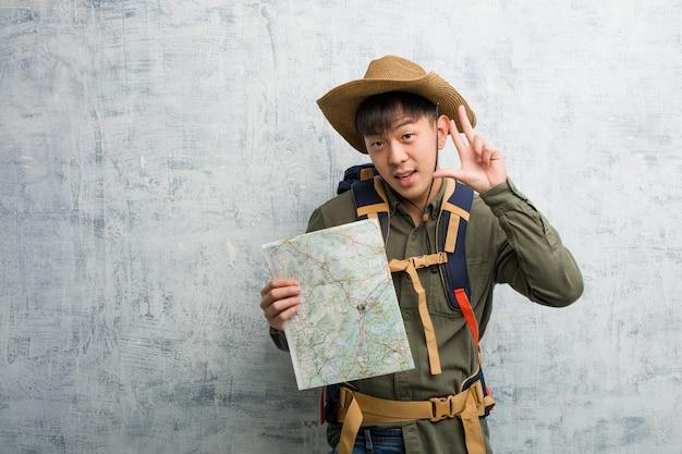 Joven chino explorador hombre sosteniendo un mapa divertido y feliz haciendo un gesto de victoria