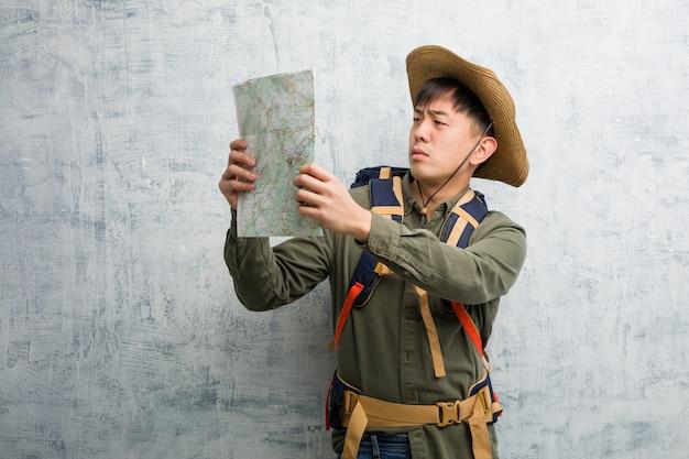 Joven chino explorador hombre sosteniendo un mapa dudando y confundido