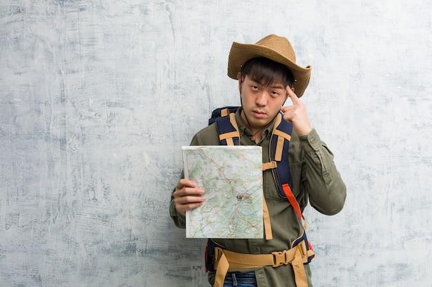 Joven chino explorador hombre sosteniendo un mapa pensando en una idea