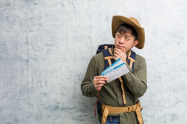 Joven chino explorador sosteniendo un boleto aéreo dudando y confundido