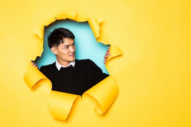 Joven chino mantiene la cabeza en el agujero de la pared amarilla rasgada. cabeza masculina en papel rasgado.
