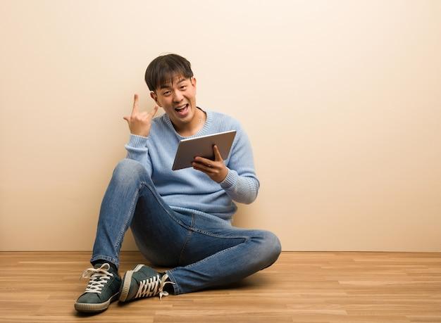 Joven chino sentado usando su tableta haciendo un gesto de rock