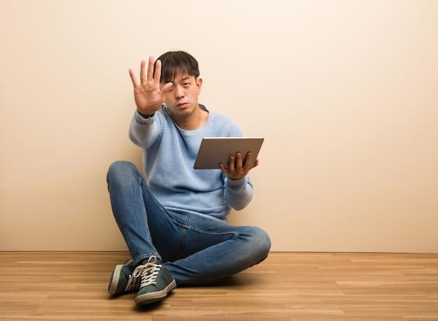 Joven chino sentado usando su tableta poniendo la mano delante