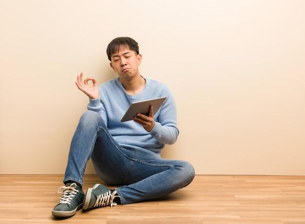 Joven chino sentado usando su tableta realizando yoga