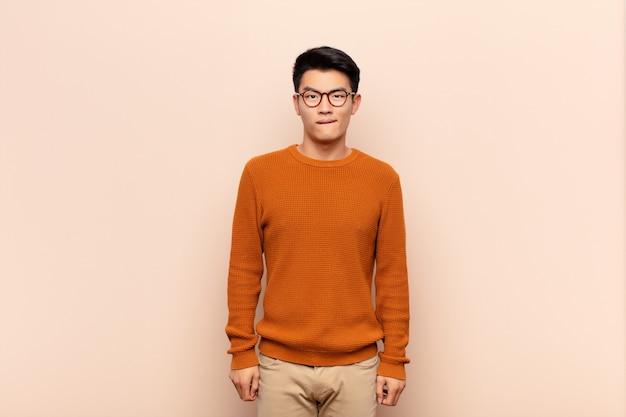 Joven chino se siente desorientado, confundido e inseguro sobre qué opción elegir, tratando de resolver el problema contra la pared de color plano