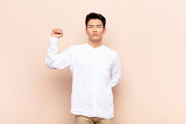 Joven chino se siente serio, fuerte y rebelde, levantando el puño, protestando o luchando por la revolución contra la pared de color plano