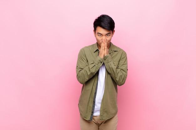 Joven chino sintiéndose preocupado, esperanzado y religioso, rezando fielmente con las palmas presionadas, pidiendo perdón contra la pared de color plano