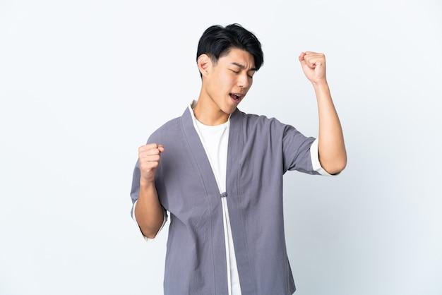Joven chino sobre aislado celebrando una victoria