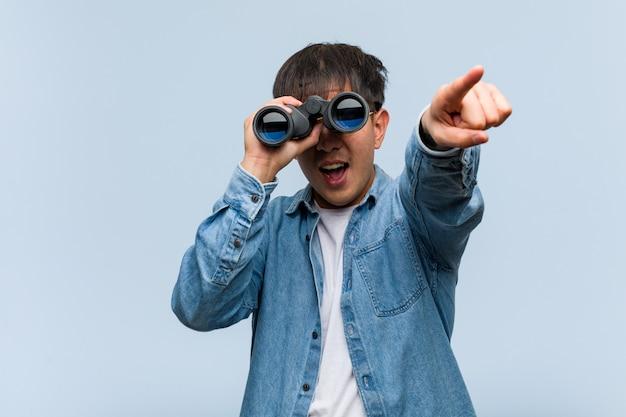 Joven chino sosteniendo un binoculares alegre y sonriente apuntando al frente