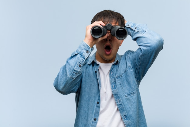 Joven chino sosteniendo binoculares preocupado y abrumado