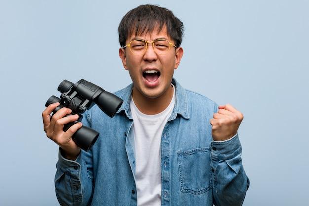 Joven chino sosteniendo un binoculares sorprendido y conmocionado