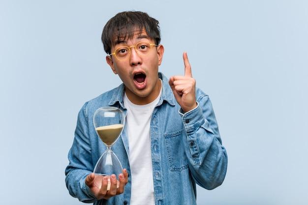 Joven chino sosteniendo un temporizador de arena con una gran idea