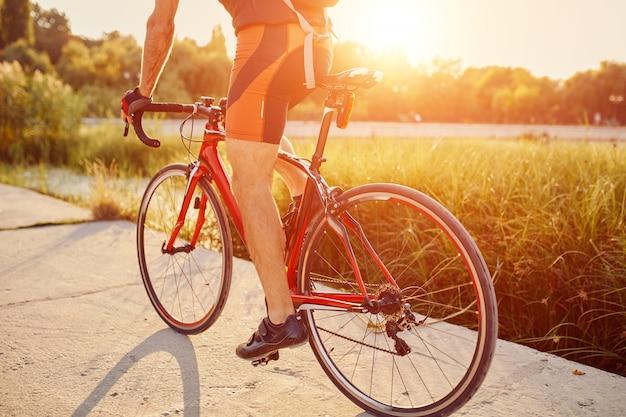 Joven está ciclismo bicicleta de carretera en la noche
