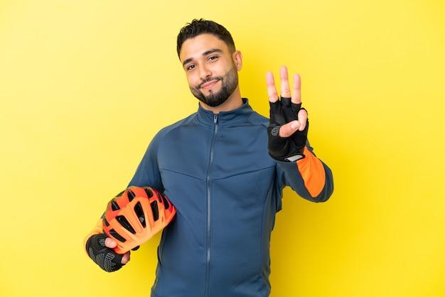 Joven ciclista árabe aislado sobre fondo amarillo feliz y contando tres con los dedos