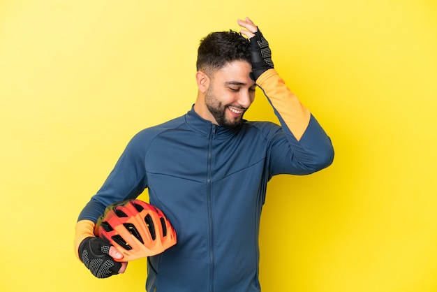 Joven ciclista árabe aislado sobre fondo amarillo se ha dado cuenta de algo y tiene la intención de la solución