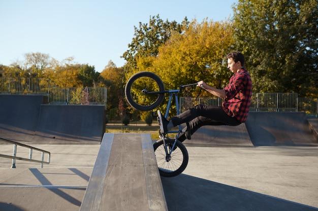 Joven ciclista de bmx salta en la pared en el skatepark. deporte de bicicleta extremo, truco de ciclo peligroso, paseos en la calle, andar en bicicleta en el parque de verano