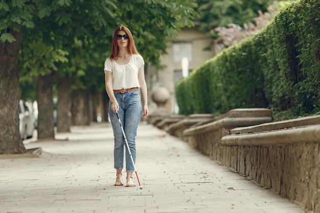 Joven ciego con bastón largo caminando en una ciudad