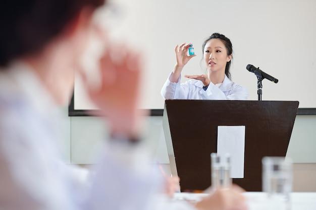 Joven científica china hablando en la tribuna sobre las pruebas de la nueva vacuna contra el coronavirus que desarrolló su equipo
