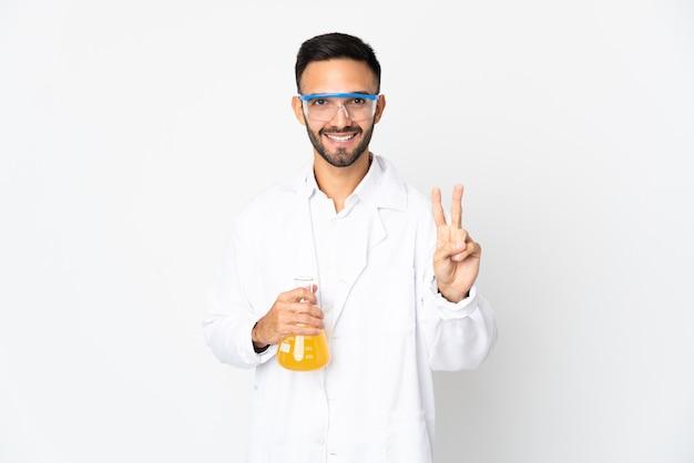 Joven científico aislado sobre fondo blanco sonriendo y mostrando el signo de la victoria
