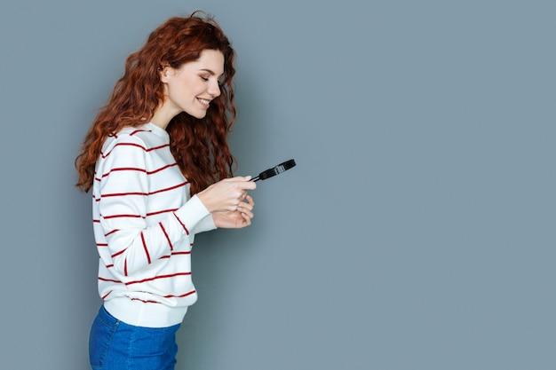 Joven científico. alegre mujer inteligente feliz sonriendo y mirando a la lupa mientras trabaja en el laboratorio científico