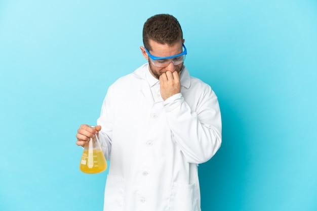 Joven científico caucásico aislado en azul con dudas