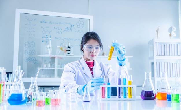 Joven científico mirando a través de un tubo en un laboratorio