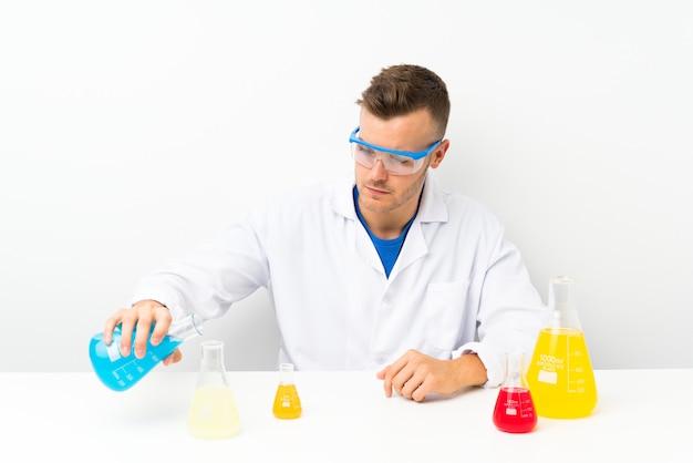 Joven científico con mucho matraz de laboratorio