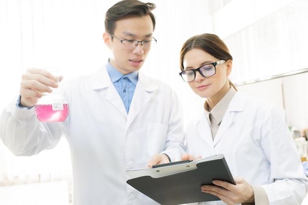 Joven científico o químico asiático sosteniendo un pico con una sustancia líquida rosa mientras le pide a su asistente que escriba sus características