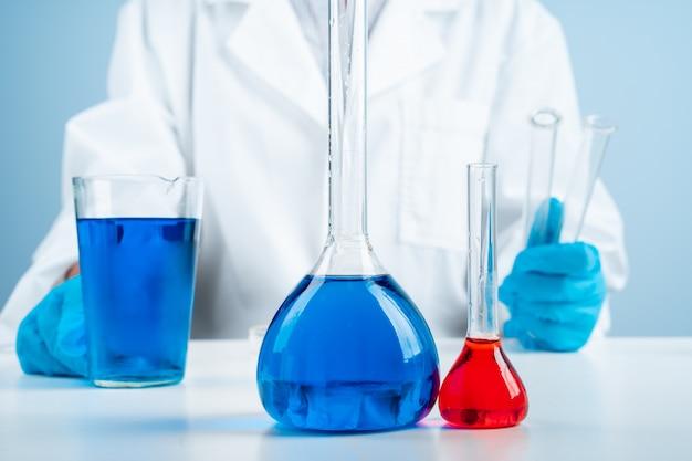 Joven científico con probeta haciendo investigación en laboratorio clínico, especialista profesional en ciencias en el trabajo,