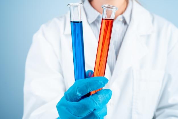 Joven científico con probeta haciendo investigación en laboratorio clínico