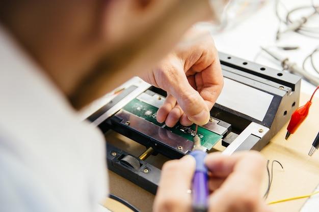 Joven científico soldando en laboratorio electrónico