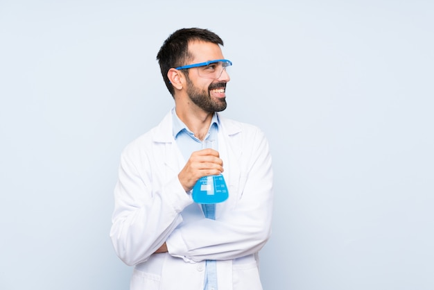 Joven científico sosteniendo frasco de laboratorio feliz y sonriente