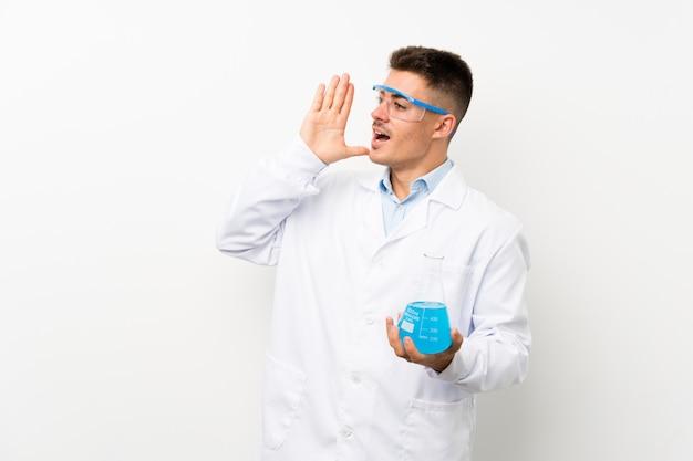 Joven científico sosteniendo frasco de laboratorio gritando con la boca abierta