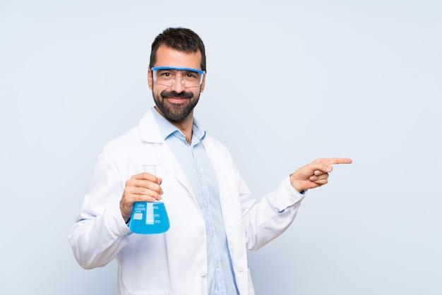 Joven científico sosteniendo frasco de laboratorio sobre fondo aislado apuntando el dedo hacia un lado