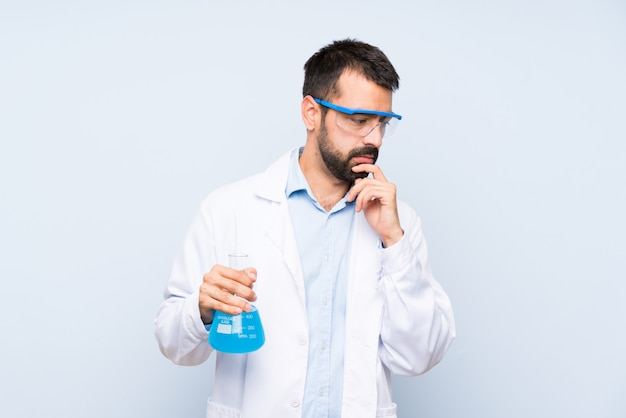 Joven científico sosteniendo frasco de laboratorio sobre fondo aislado que cubre la boca y mirando hacia un lado