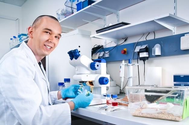 Joven científico trabaja con ratones de laboratorio.